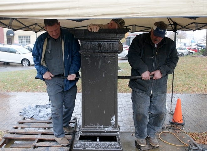 Three men lift the restored World War I Memorial Fountain on the northeast lawn of the Madison County Courthouse, Wednesday, November 14.