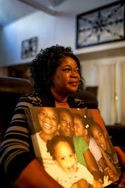 Martha Epperson cradles a canvas portrait of her daughter Tory Howard with the four children she took on after her daughter's passing at her home in Jackson, Tenn., on Wednesday, Nov. 7, 2018.