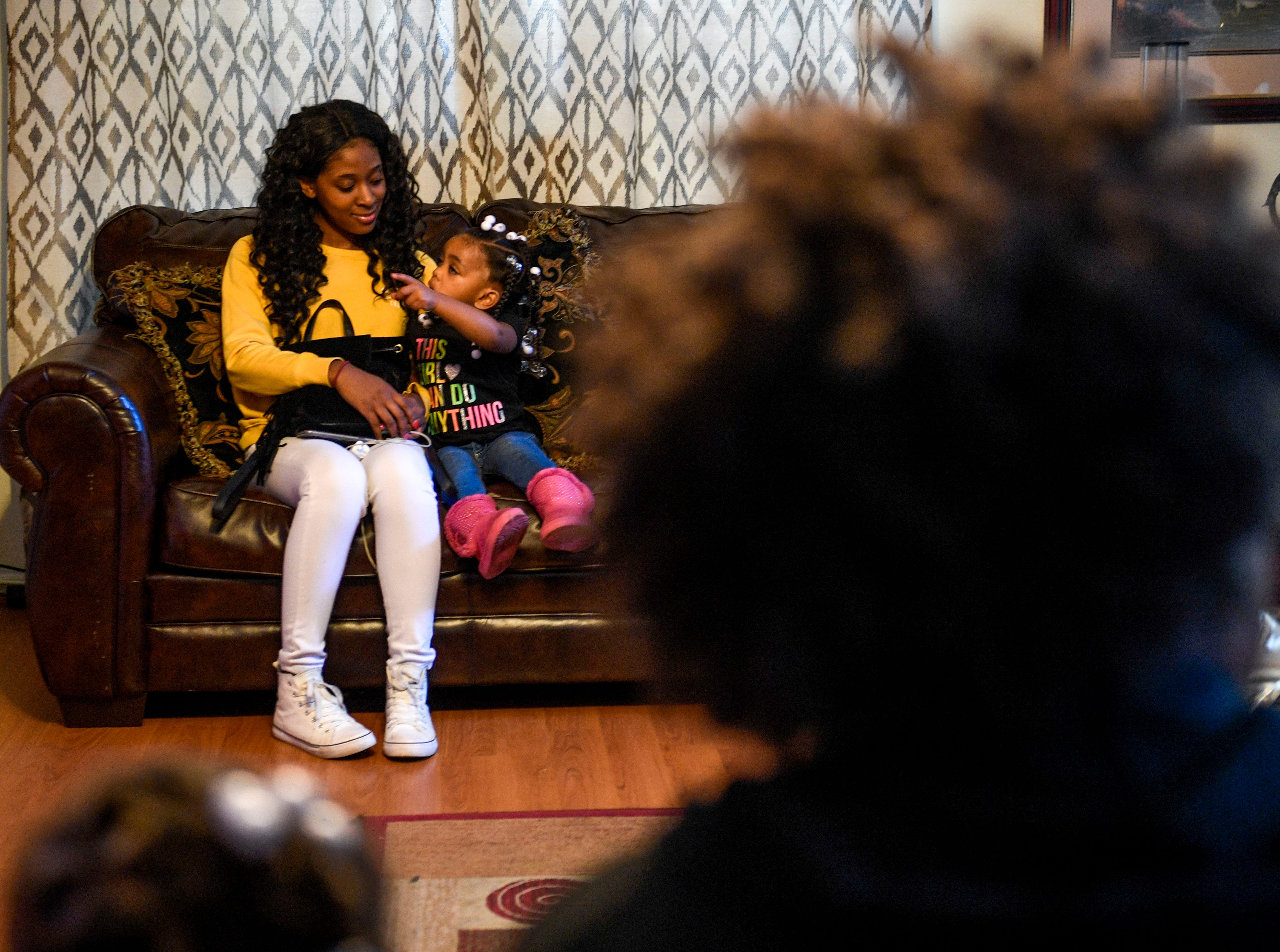 Peyton Howard, 2, points to the television screen while playing with Maya Kemp, both Tory Howard's nieces, at the home of Martha Epperson in Jackson, Tenn., on Wednesday, Nov. 7, 2018.