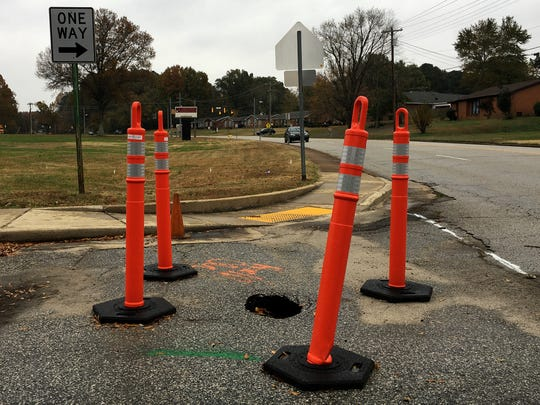 Orange traffic cones surround a small sinkhole that formed at the exit of Andrew Jackson Elementary School.