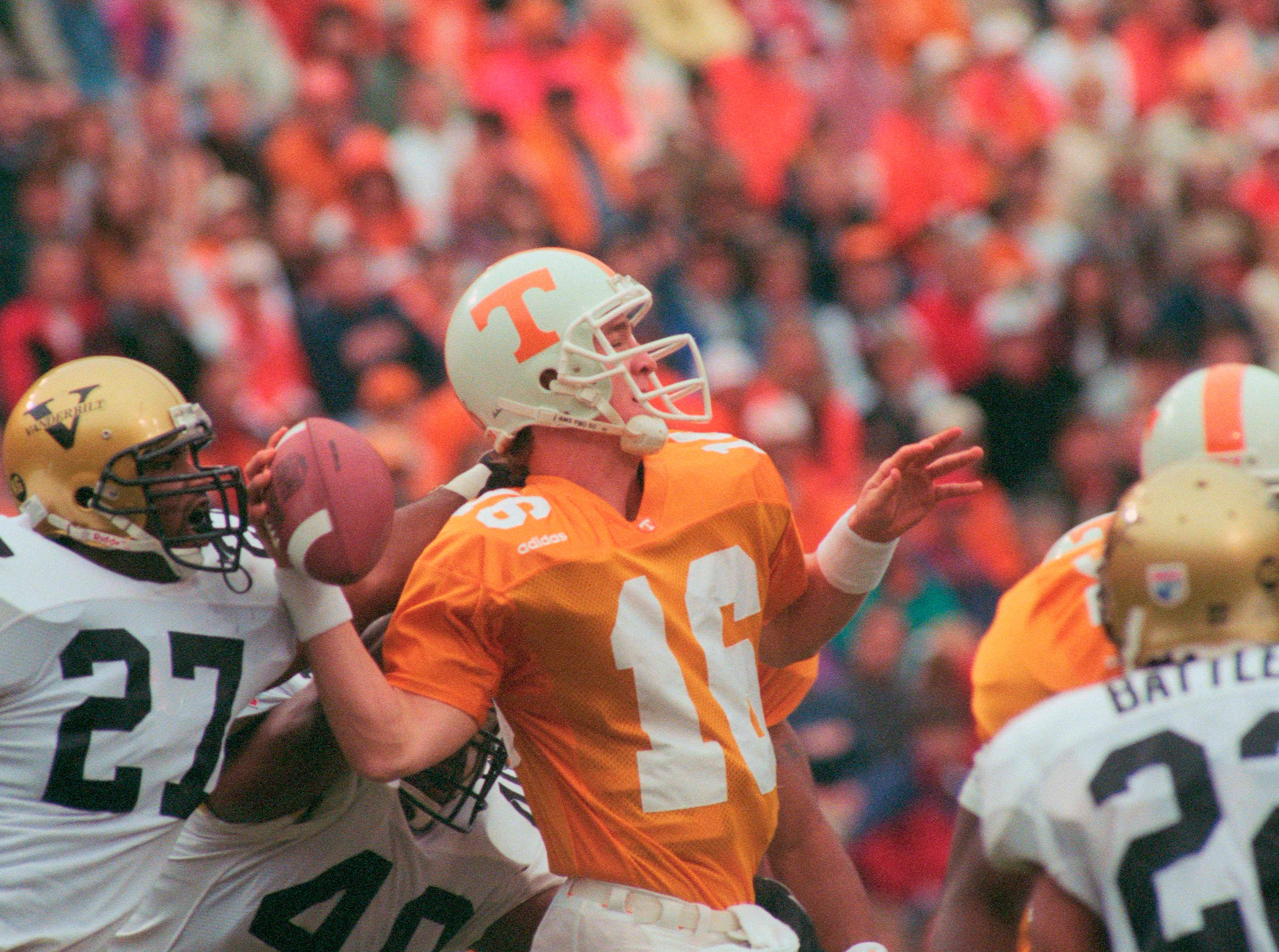 Tennessee quarterback Peyton Manning is pressured by Vanderbilt defenders on Nov. 29 1997, at Neyland Stadium. Manning went 12-27 passing with one interception and one touchdown as the Vols eked out a 17-10 victory.