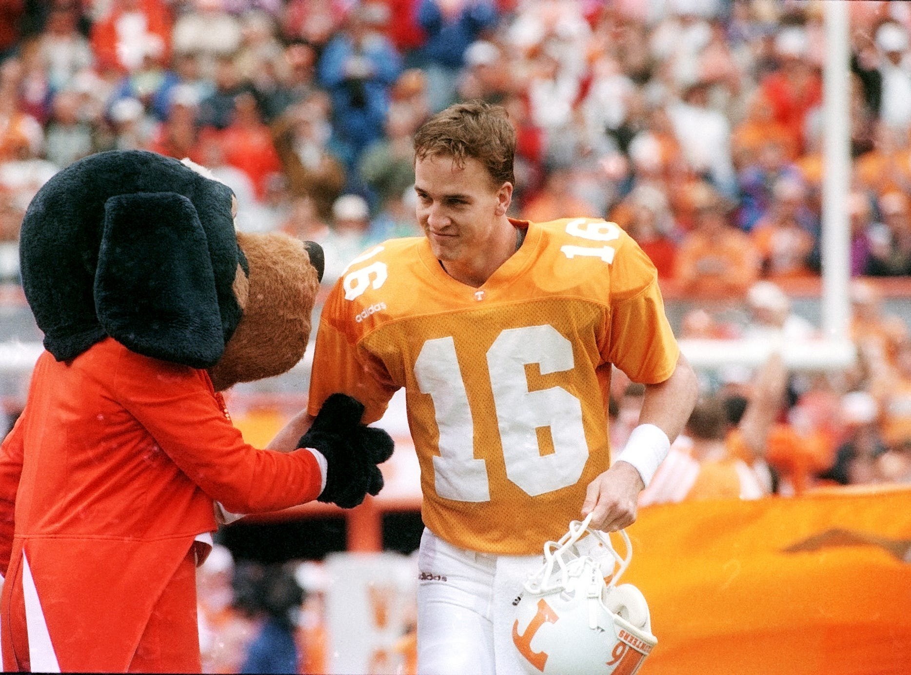 Tennessee quarterback Peyton Manning is greeted by Vol mascot Smokey before the Vanderbilt game Nov. 29, 1997, at Neyland Stadium. It was Manning's final home game.
