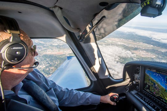 Metropolitan Knoxville Airport Authority president Bill Marrison pilots a Cirrus aircraft near McGhee Tyson Airport, seen through the window at right, on Friday, Sept. 7, 2018. Marrison announced his retirement and will leave his post on December 31 after 36 years with MKAA.