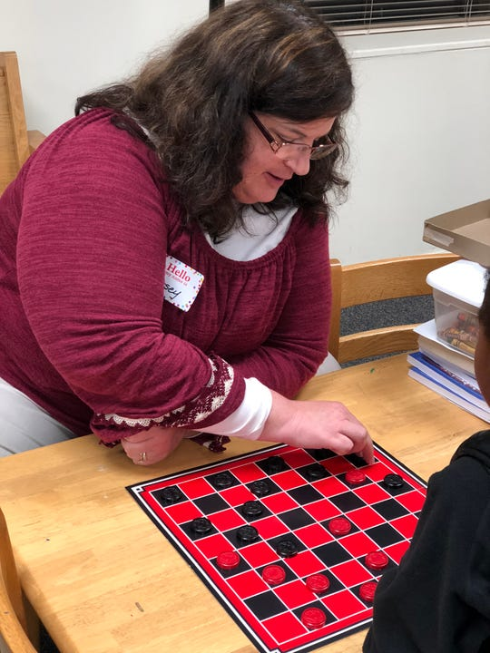 Church of the Good Shepherd member Casey Collins volunteered to open the church for the Monday night guests and played checkers with one of the little girls staying the night.