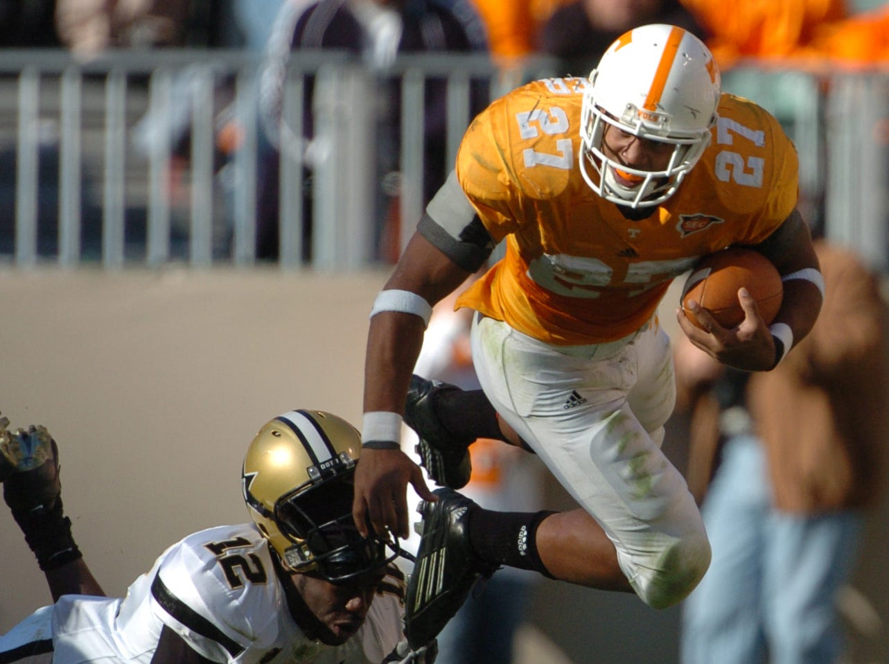 UT's Arian Foster knocks off the helmet of Vanderbilt's Kelechi Ohanaja (12) in the first half of the game at Neyland Stadium Saturday afternoon. Foster finished the game with 40 carries for 223 yards and 2 touchdowns on 11/19/2005.