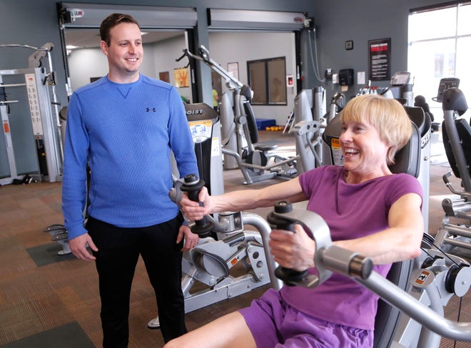 Mitch Barker looks on as Cheryl Finnell work out with a pec fly machine Wednesday, November 14, 2018, at Faith West in West Lafayette. Barker is a certified personal trainer with the Faith Community Center gyms.