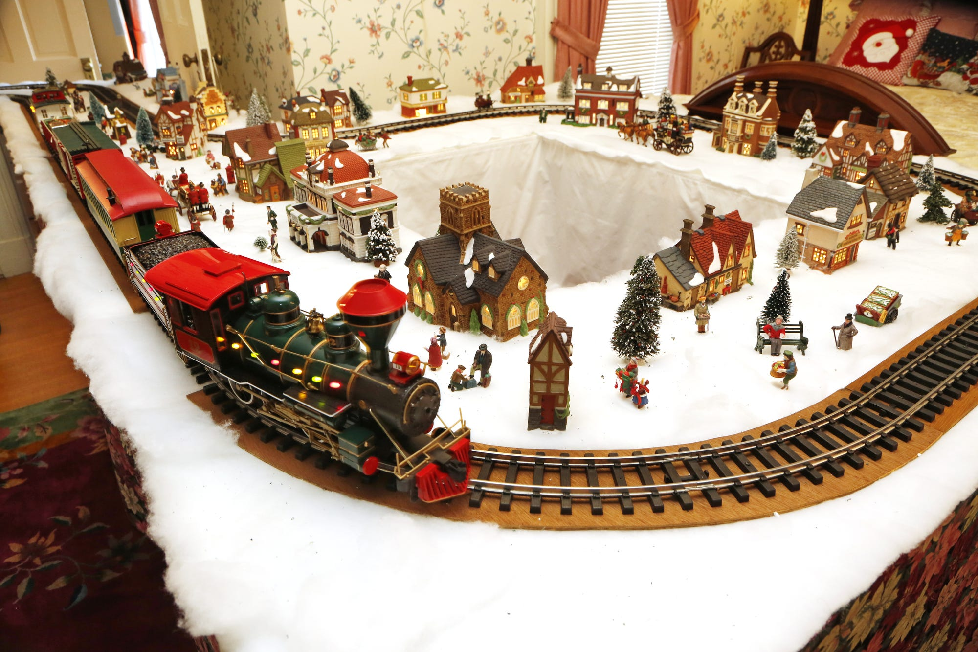 A G scale train winds through a holiday setting in two bedroooms, a bathroom and a closet inside the Haan Mansion Museum in Lafayette.