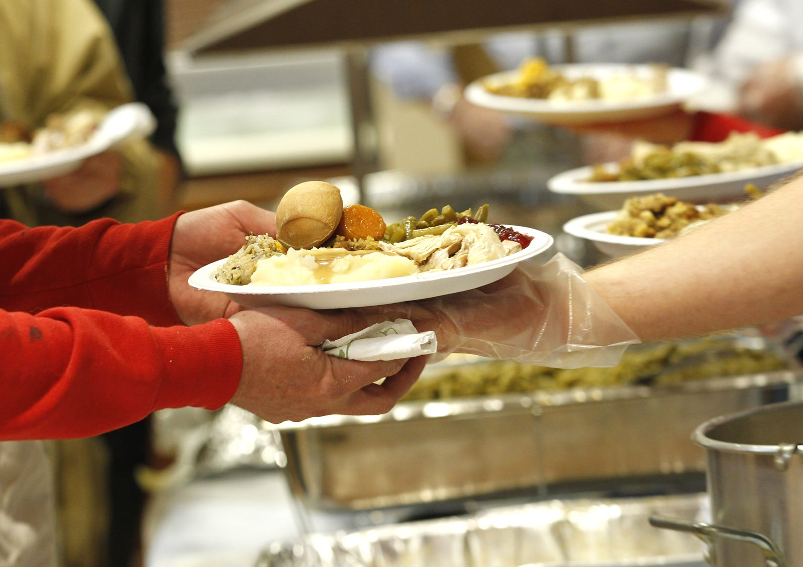 A guest receives a plate loaded with hot, delicious food during Lafayette Urban Ministry's Community Thanksgiving Celebration Thursday, November 22, 2012, at Central Presbyterian Church in Lafayette.