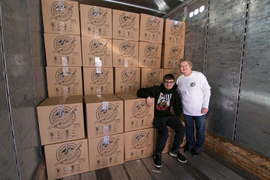 """""""Operation Christmas Child"""" drive director Anne Kelvert and Caleb Madden, son of Brighton Christian Church lead pastor Jacob Madden, shown Wednesday, Nov. 14, 2018, climbed into a semi truck trailer containing 108 cartons containing 1,732 shoe boxes filled with Christmas gifts to be distributed around the world. Members of the Brighton Township church organized the local effort."""