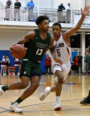 Trinity guard David Johnson (13) attempts to drive past the defense of Ballard guard Tyron Duncan (5) during the second half of their 7th region championship game, Monday, March 5, 2018 in Louisville Ky.