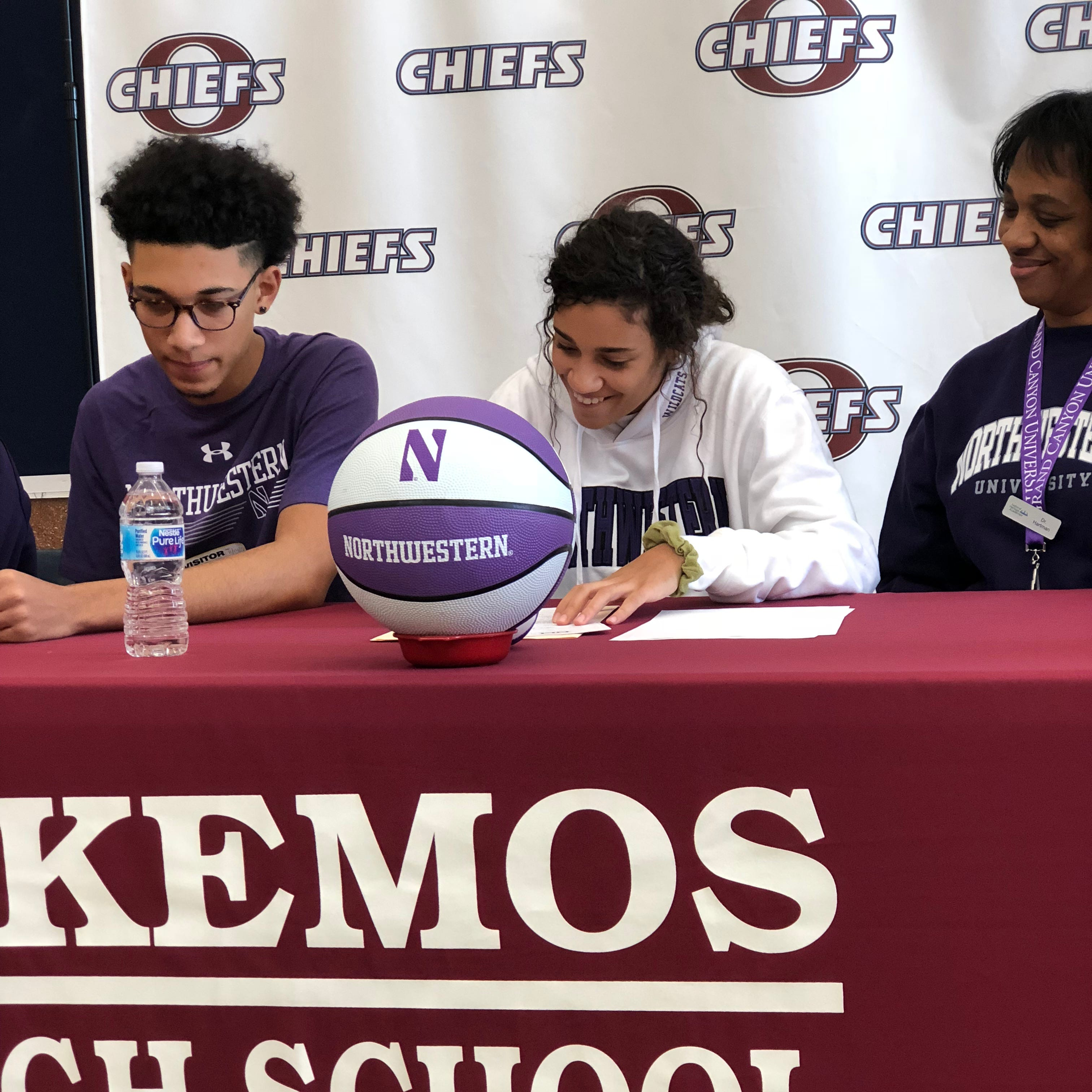 With her brother and mother looking on, Okemos senior Laya Hartman, center, signs her letter of intent to play basketball at Northwestern. Hartman was among several Lansing area athletes that signed with schools on Wednesday.