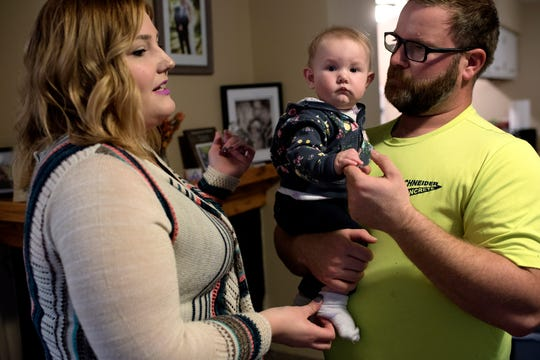Katie Esch, left, and her husband, Lee, interact with their 5-month-old daughter, Violet, after work on Wednesday, Nov. 14, 2018, in Grand Ledge. The family is struggling with a water bill that hit $2,700.