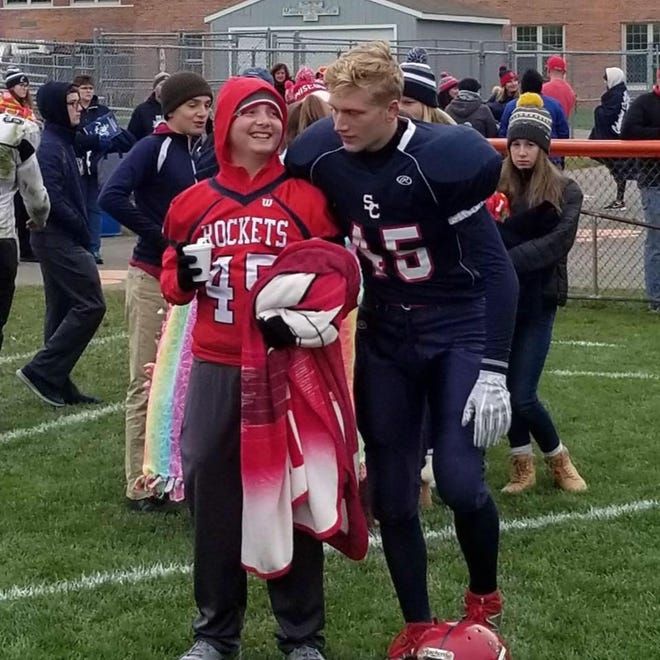 Morgan Gorst, left, is pictured with his older brother after a football game. Morgan, 13, who was diagnosed with glioblastoma in September 2018, died Tuesday.