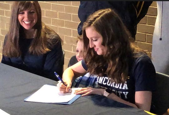 Wausau West senior Isabella D'Burke signs her national letter of intent to run track at Concordia University Wednesday morning.