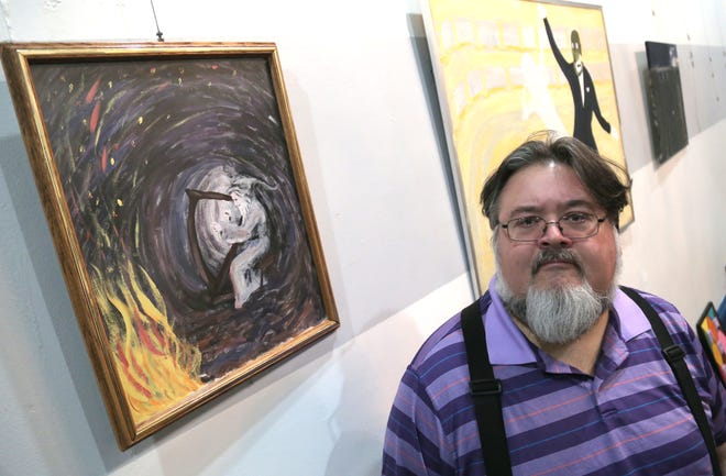 Mark Jordan stands with one of his paintings exhibited at Green Room Gallery. His show opens Friday.