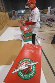 Wanda Lewis fills gift boxes at Freedom Ridge Church on Wednesday while volunteering for the Samaritan's Purse Operation Christmas Child program.