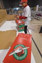 Wanda Lewis fills gift boxes at Freedom Ridge Church on Wednesday while volunteering for the Samaritan's Purse Operation Christmas Child program.