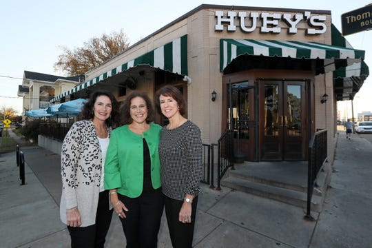 Sisters Ashley Robilio, from left, Samantha Dean and Lauren Robinson at the original Huey's in Midtown. The siblings run the business their father created.