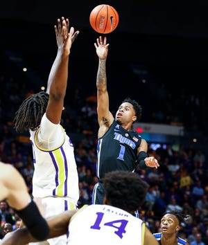 Memphis guard Tyler Harris (middle) goes up over the LSU defense for a shot Tuesday.
