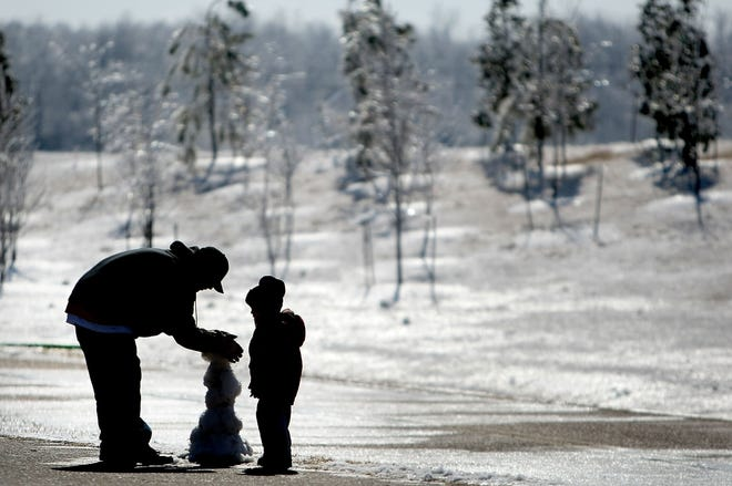 Jan. 31, 2010  -  Jason Jenkins and his son Jordan Jenkins, 3, try to make a little snowman at Shelby Farms Sunday afternoon coddling together small chunks of ice.