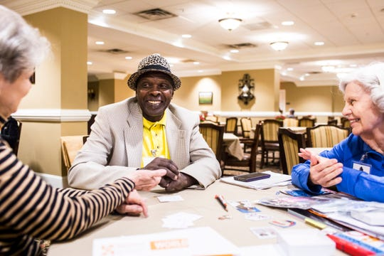 Ezekia Ruhara, center, smiles while Modine Bolen, left, and Ann Powell, right, work with him during a English as a Second Language study group session at Trezevant Manor on Nov. 14, 2018.