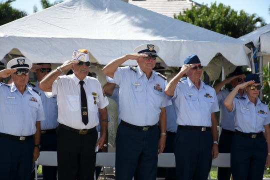 Veterans salute during the Pledge of Allegiance at a Marco Island Veterans Day celebration.