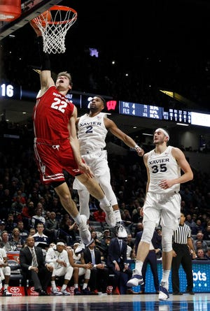 Wisconsin forward Ethan Happ throws down two of his game-high 30 points as Xavier guard Kyle Castlin (2) tries to defend during the first half on Tuesday night in Cincinnati.