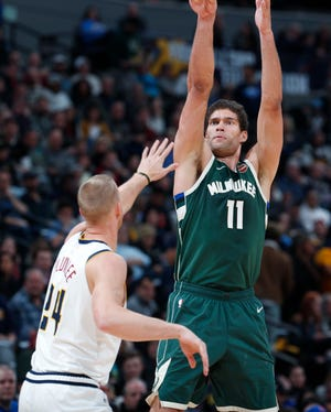 Milwaukee Bucks center Brook Lopez, right, makes a three-point basket over Denver Nuggets forward Mason Plumlee in the second half of an NBA basketball game Sunday, Nov. 11, 2018, in Denver. Milwaukee won 121-114. (AP Photo/David Zalubowski) ORG XMIT: CODZ125