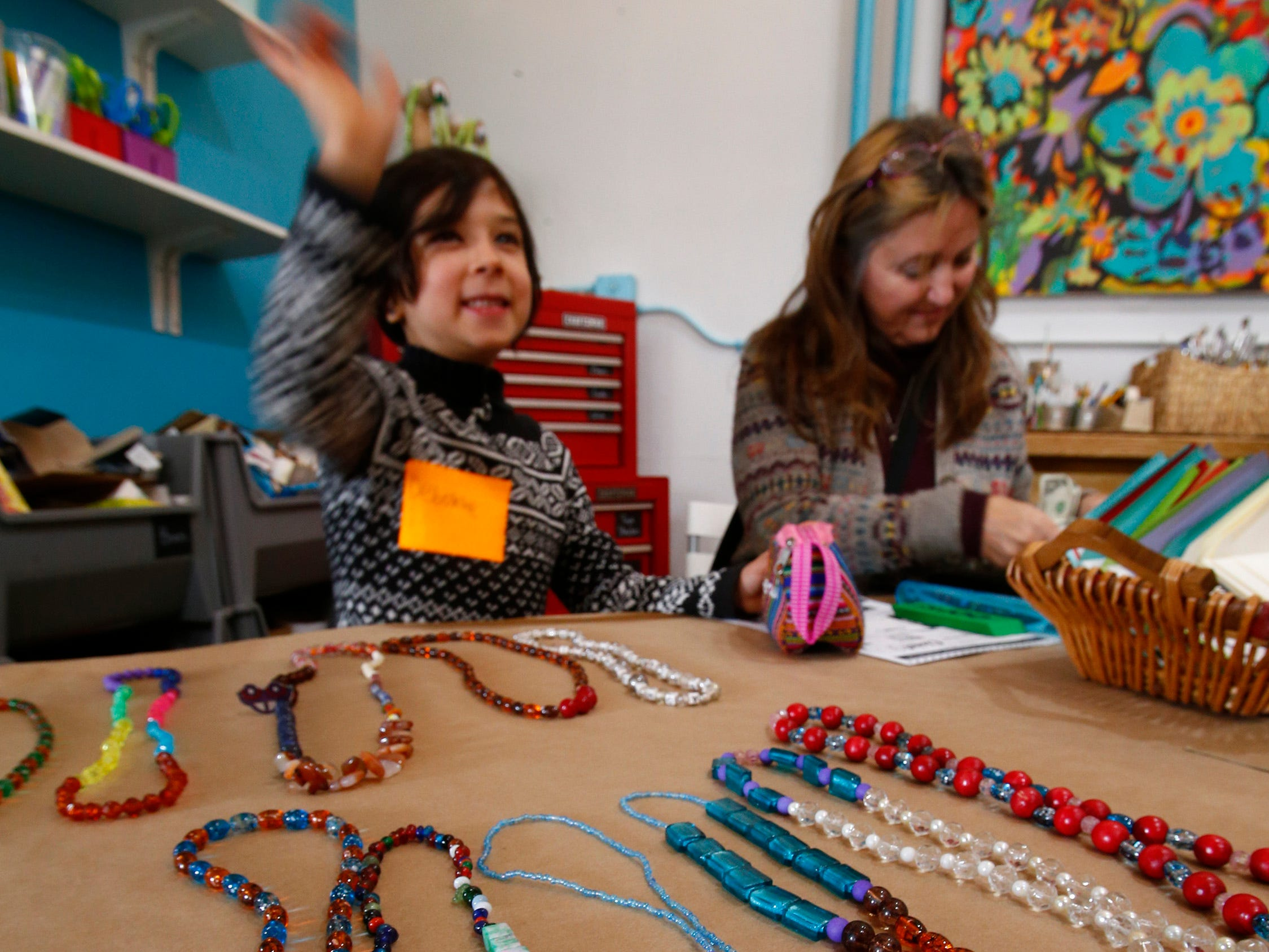 Debonne Melby-Gibbons waves to a friend while selling necklaces with Leslie Gibbon, Debonne's grandmother from Iowa, during the Cloud 9 Workshop's Kidpreneur Fair that featured 15 children in grades 1 through 5 selling products they created.