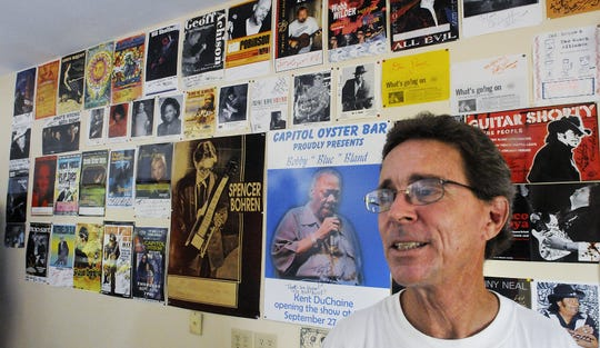 Lewis Mashburn stands next to posters of acts that he has brought to Montgomery, in the lobby of his Capitol Oyster Bar.