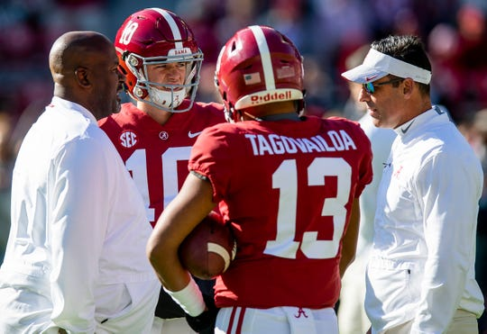 Alabama quarterback Mac Jones (10) and quarterback Tua Tagovailoa (13) talk with offensive coordinator Mike Locksley, left, and quarterbacks coach Dan Enos , right, before the Alabama vs. Mississippi State game at Bryant Denny stadium in Tuscaloosa, Ala., on Saturday November 9, 2018.