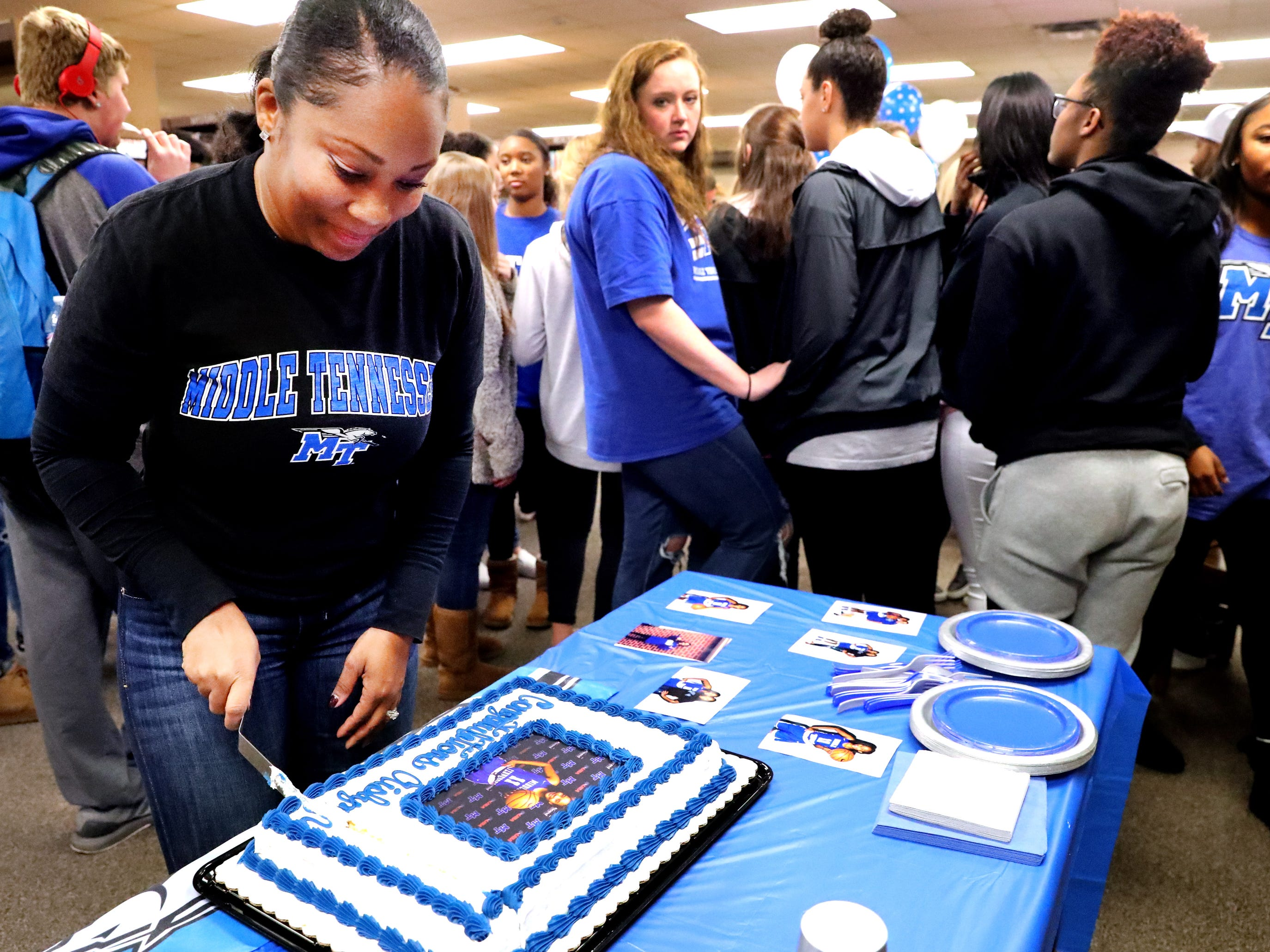 Sherry Hayes the mom of Riverdale's Aislynn Hayes cuts a cake after her daughter Aislynn Hayes signed to play basketball at MTSU on Wednesday, Nov. 14, 2018.