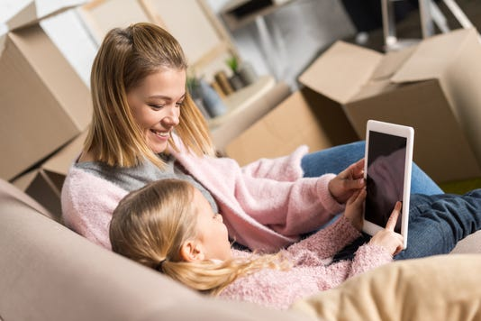 Happy Mother And Daughter Using Digital Tablet With Blank Screen While Moving Home