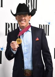 Aaron Watson holds his medal on the red carpet at BMI's 2018 Country Music Awards on Nov. 13 in Nashville.