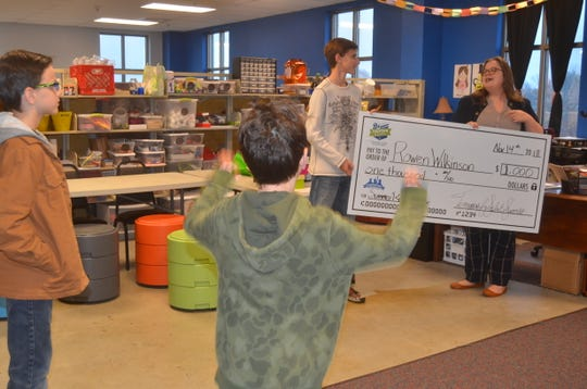 Rowen Wilkinson's brothers Ryland and Sawyer celebrate while Rowen receives a $1,000 scholarship from Tennesseans for Student Success for reading the most in the state in his age group this summer.