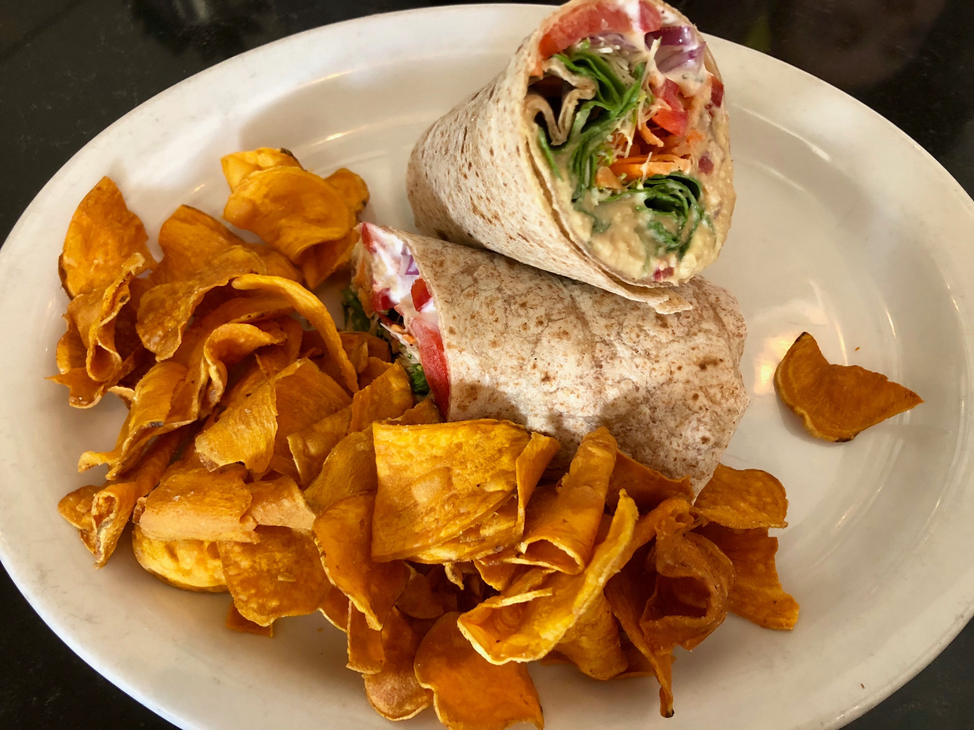 A veggie wrap brimming with hummus, tzatziki sauce and local vegetables at The Local restaurant in North Naples.