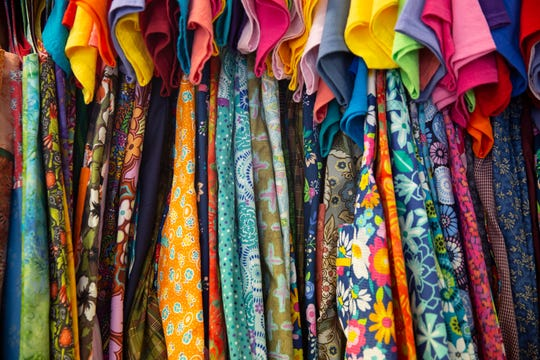 """Dresses created by """"Sewing for Hope"""" hang on a rack, Tuesday, Nov. 13, 2018 at Trinity Episcopal Church in Naples. The dresses made by the group who get together every month to make colorful dresses for girls living in a Tanzania."""