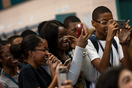 From the left, Reginae Celiant, Kency Cesar and Amir Churchwell, current students of Gulf Coast High School take videos and photographs of their athlete friends, Sydney Eugene and Yasmeen Chang, Wednesday morning, Nov. 14, 2018, during the College Singing Day.