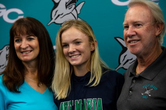 Sierra Studer, a Gulf Coast High School golfer, poses for a photograph with her parents at the end of the College Signing Day event at the media center of Gulf Coast High School on Wednesday, Nov.14, 2018.