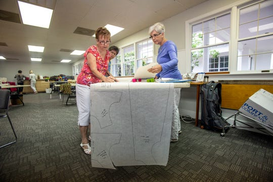 Sewing for Hope members Nancy Watson, left, Barbara Caldwell and Judy Saunders work on a dress, Tuesday, Nov. 13, 2018 at Trinity Episcopal Church in Naples.