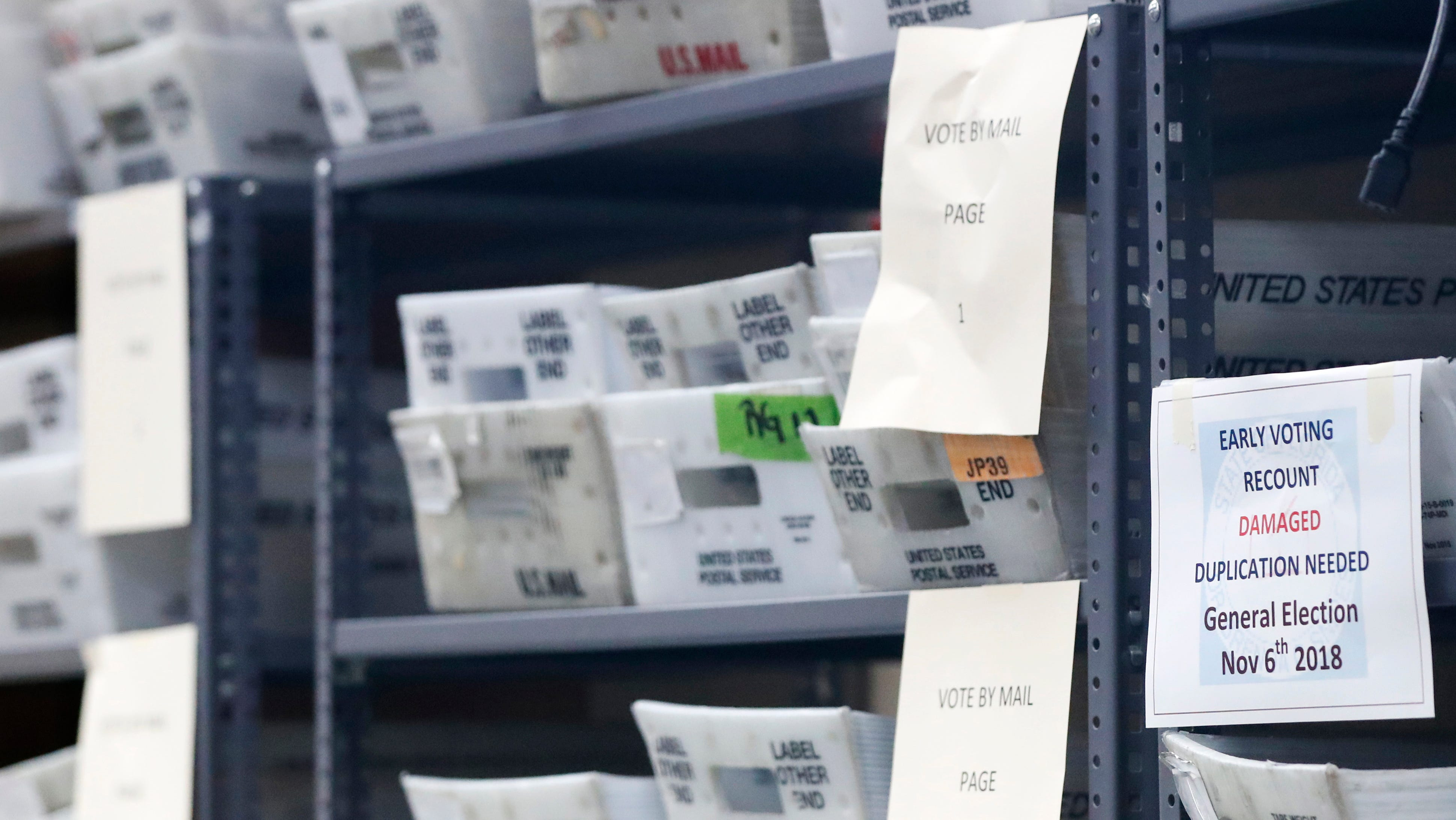 Bins filled with ballots are stacked at the Broward County Supervisor of Elections office as employees count ballots during a recount Wednesday, Nov. 14, 2018, in Lauderhill, Fla.