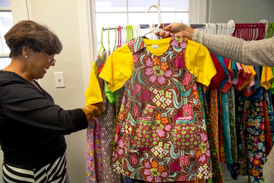 "BJ Ferriel, left, and Lis Wilson looks through a rack of dresses created by members of ""Sewing for Hope"", Tuesday, Nov. 13, 2018 at Trinity Episcopal Church in Naples."