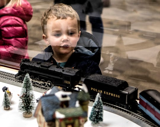 "Max Hoben, 3, looks through the glass as model trains roll by at the Granville Public Library's 2017 train display. This year, the theme is ""Jurassic."""
