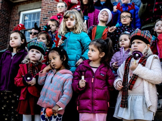 The Welsh Hills School Handbell Choir performs carols outside the post office during the 2017 Granville Christmas Candlelight Walking Tour.