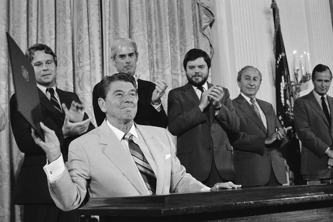 President Ronald Reagan holds up the Captive Nations Week Proclamation, after signing it during a ceremony at the White House, July 16, 1984, Washington, D.C. Applauding the President from left are, Rep. Christopher Smith, R-N.J.; Rep. John Edward Porter, R-Ill.; and Kenneth Tomlinson, head of Voice of America. Man second from right is unidentified. Vice president George H.W. Bush is at right.
