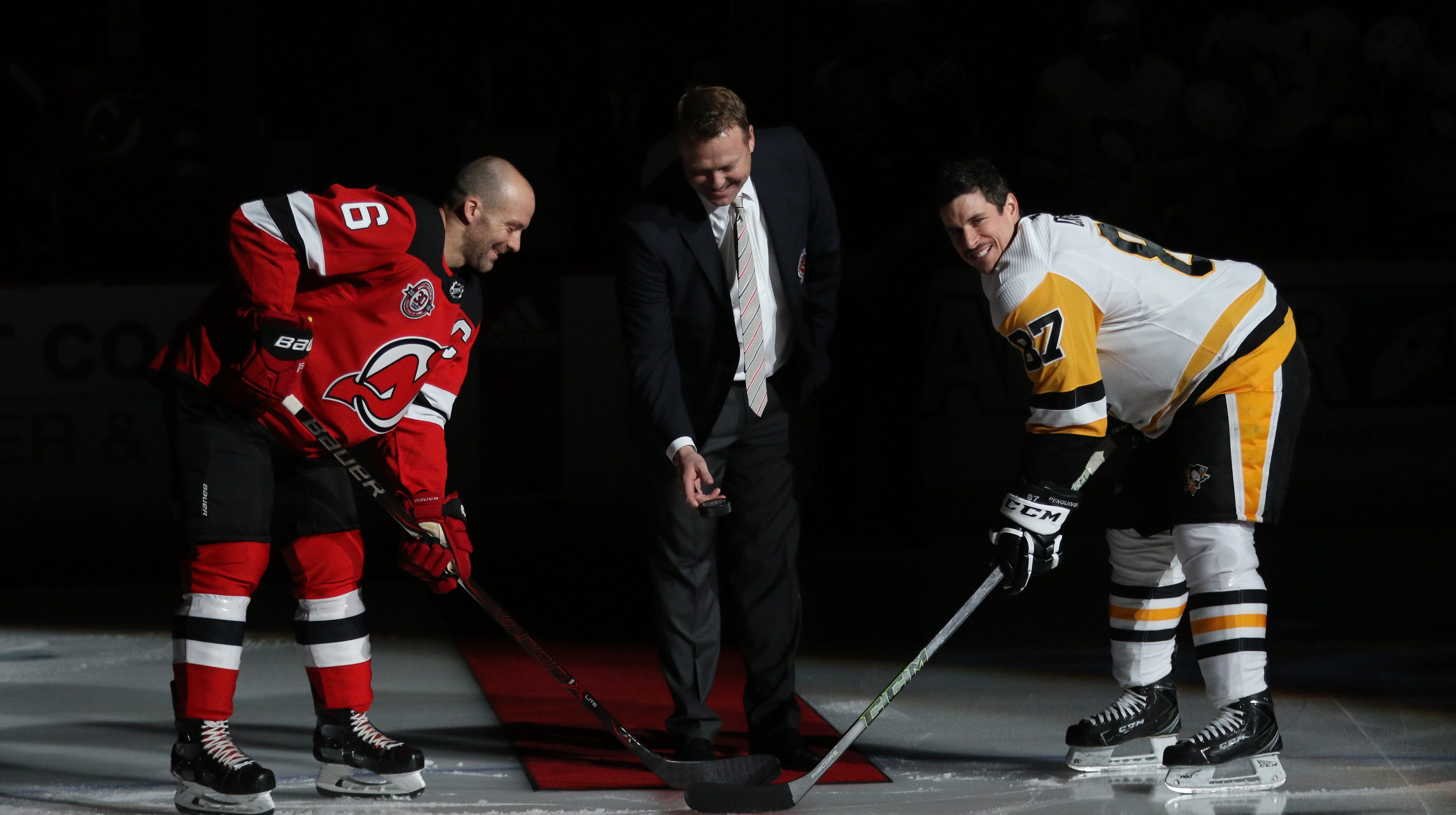 Martin Brodeur stands between Andy Greene of the...
