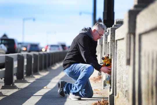 Robert Popp of Dumont, who is lobbying Little Ferry, Ridgefield Park and the NJDOT to name the westbound walkway of the route 46 span across the Hackensack River in honor of his sister, Gloria,  lays flowers at the spot where his 15 year old sister was killed by a hit-and-run driver there in November 1969. Photographed 0n 11/14/18.  If successful the memorial would occur on the 50th anniversary and call attention to the rising number of NJ pedestrian fatalities.