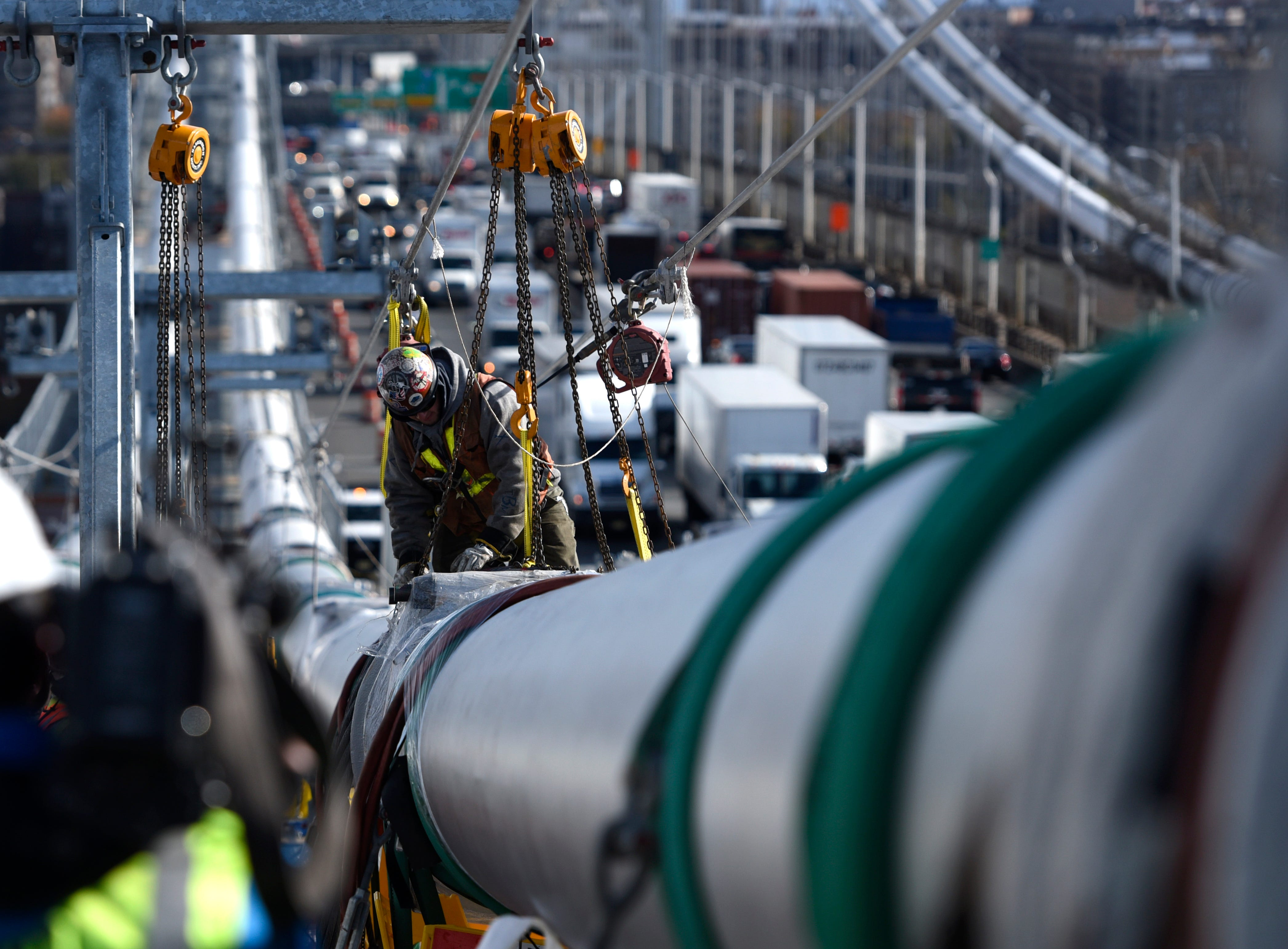 A construction worker works on one of the main cables of the George Washington Bridge on Wednesday, Nov. 14, 2018. The main cables will need to be temporary replaced as they are rehabilitated, and the suspender ropes will be replaced entirely as they are all original components of the bridge, built in 1927. The Port Authority estimates the project will take six to seven years.