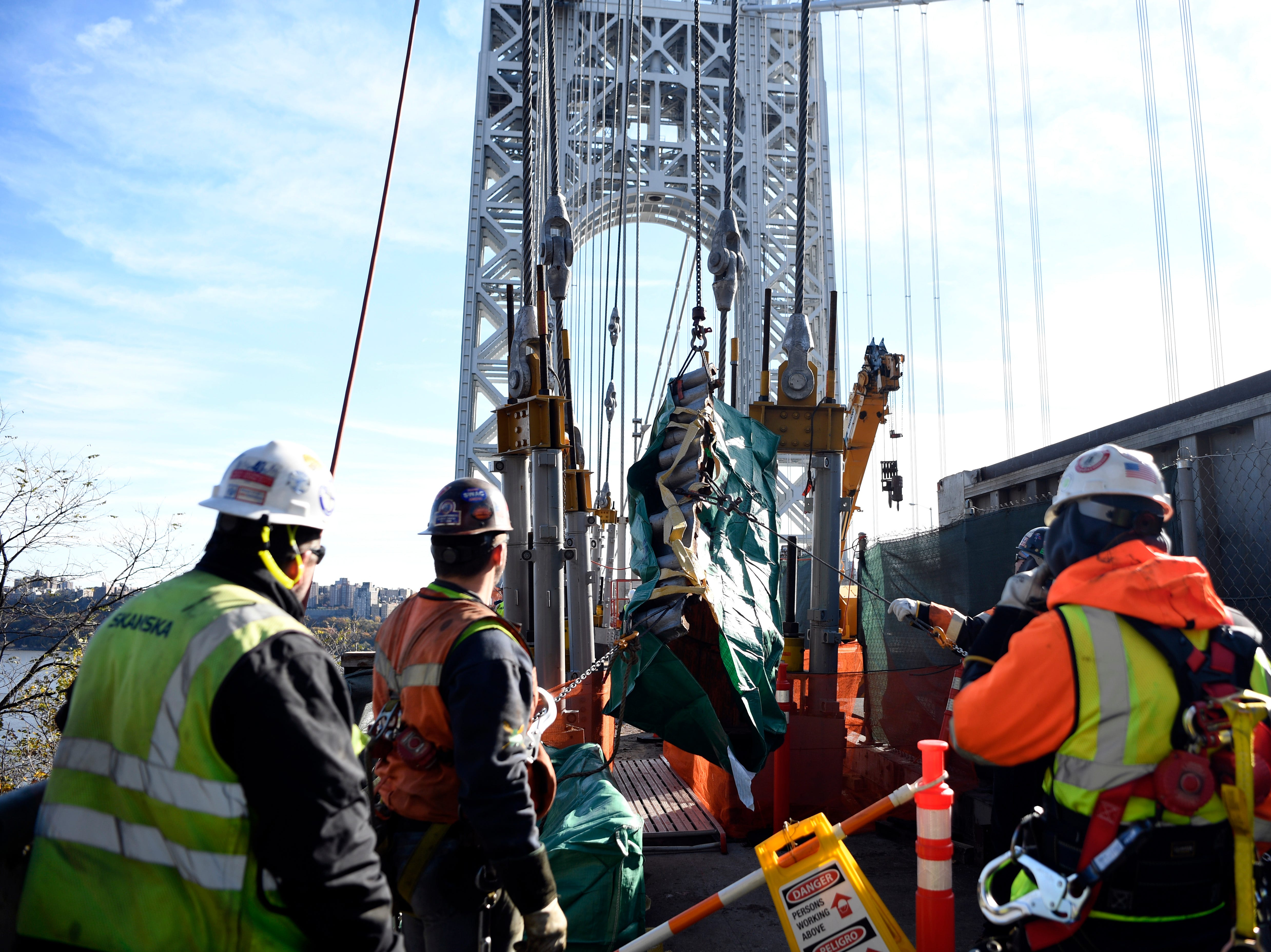 Construction workers lower down cables to be rehabilitated as a part of the Port Authority's program to rehab and replace cables and suspender ropes on the George Washington Bridge on Wednesday, Nov. 14, 2018, in Fort Lee.