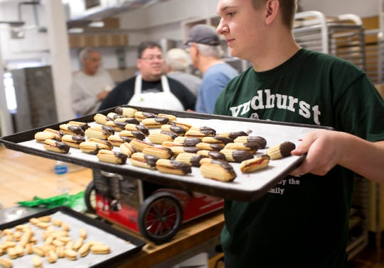 Lyndhurst Pastry Shop employee Seb Lapinski moves a tray of freshly dipped jelly finger cookies at the shop on Saturday.   Erica Yoon/Special to NorthJersey.com